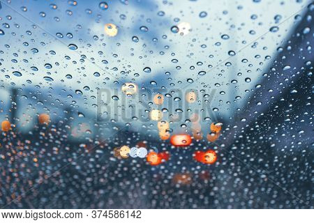 Driving Car On Metropolis Road In Trafic Jam With Raindrop Over The Wind Shield, Rainy Season