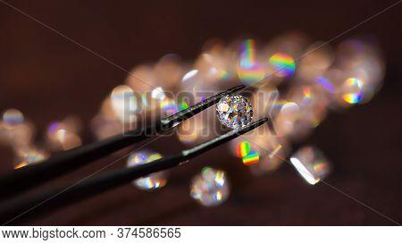 Diamond In Tweezers On A Dark Background With Diamonds Group Soft Focusing