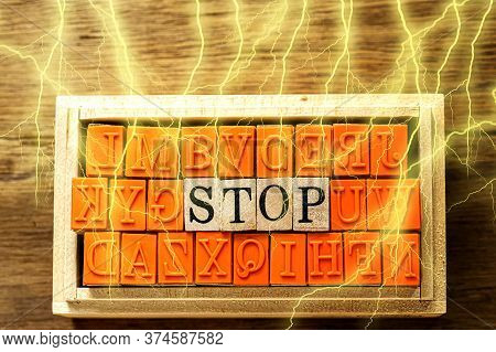 Stop - Isolated Abstract In Wood Type Stamps And Lightning Or Thunder Against Wooden Background And