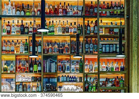 A Wide Range Of Luxury Alcohol Bottles In The Restaurant Bar.  The Shelves Are Illuminated With Warm