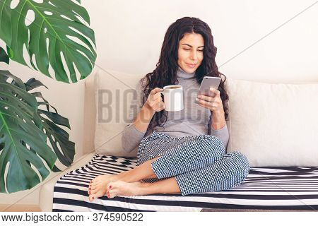 Caucasian Woman Using Smartphone While Relaxed Drinks Morning Coffee Sitting Comfortably On The Couc