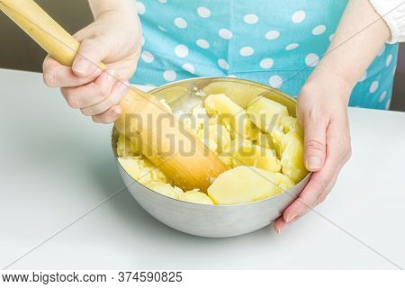 Cooking Potato Pie Fillings (quiche, Dumplings). Female Hands Hold A Wooden Potato Masher In The Hom