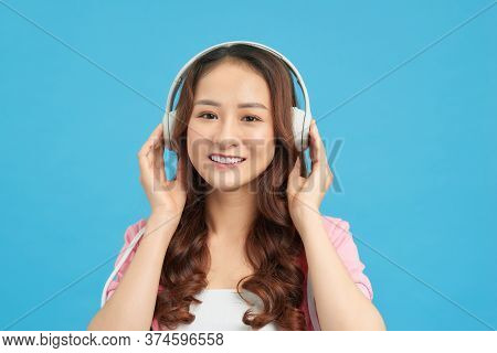 Happy Asian Teenage Girl Listen The Music Song In Wireless Headphone From Mp3 Player Technology. Rel