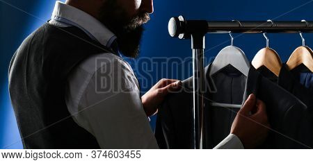 Man Suit, Tailor In His Workshop. Male Suits Hanging In A Row. Men Clothing, Boutiques. Tailor, Tail