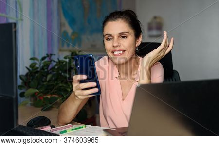 Smiling Young Woman Working Home Near Laptop, Shrugging With Hand Sideway, Holds Phone, Smile Saying