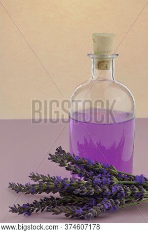 Lavender Water. Lavender Extract.lavender Essence In Transparent Bottle Lavender Flowers On A Purple