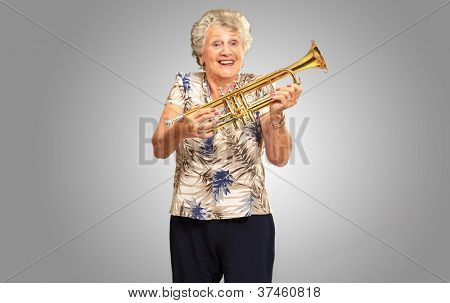 Portrait Of A Senior Woman Holding A Trumpet On gray Background poster