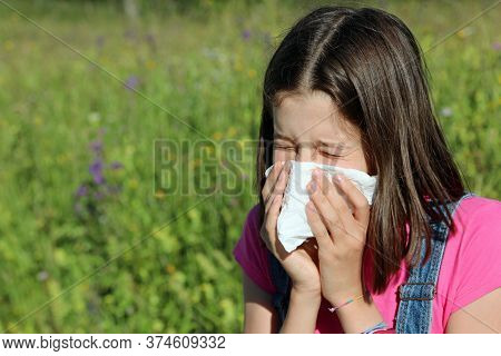 Young Girl Allergic To Pollen Blows Her Nose With A White Handkerchief And Sneezes