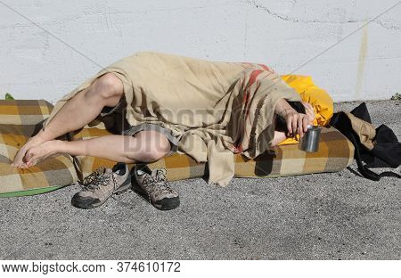 Homeless Man Begging Passersby In A City Street While Resting Under A Dirty Blanket And A Dirty Matt