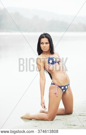 Beautiful Smiling Young Woman With American Flag On The Beach On Independence Day