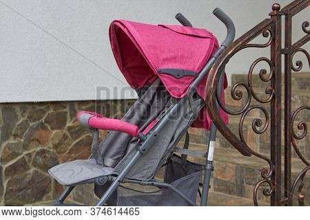 Pink Stroller Near The Railing, There Is An Empty Cart Near The Stairs Near The Metal Railing