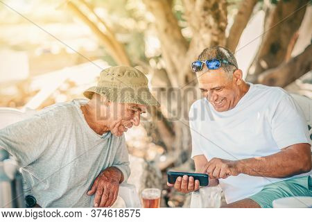 Two Positive Smiling Silver Surfer Senior Man Use Smartphone And Drinking Tea. Active Healthy Senior