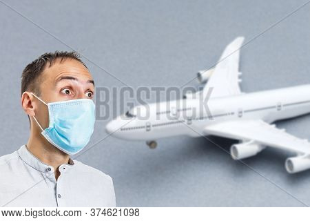Man In A Protective Mask On The Background Of The Plane. Protection Against Coronavirus And Gripp