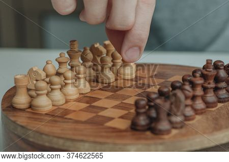 Chess Board And Chess Pieces, Wooden Small Chess Pieces On A Chess Board. Childrens Hand, Fingers Ho