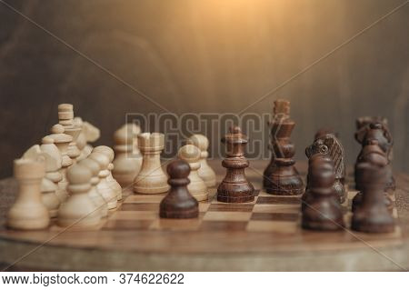 Chess Board And Chess Pieces, Wooden Small Chess Pieces On A Chess Board. A Dark Background, Light S