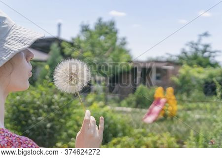 Teen Girl In A Hat Blowing Dandelion, Rustic Nature, Summer Vacation, Country Farm, Rural Lifestyle