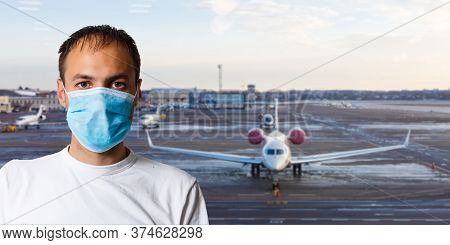 Man Wearing A Mask For Prevent Virus In International Airport Lounge With His Luggage. Protection Ag