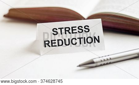 Piece Of Paper With Text Stress Reduction On The Background Of Books, Pens, On A White Background