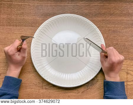 A Kid Is Hungry. An Empty White Plate On A Wooden Table. Fork And Knife. Fasting, Dieting Concept