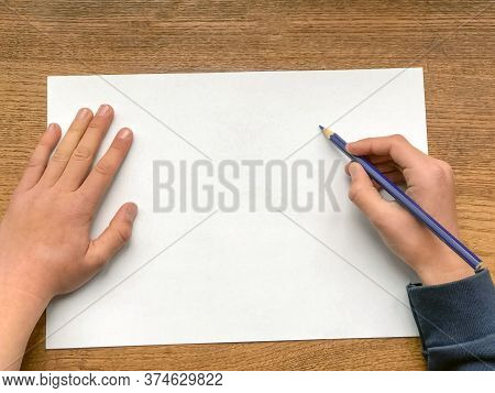 Boy's Hands With Pencil On White Sheet Of Paper Ready To Write Or Draw. Close-up. Copy Space. Educat