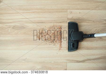 A Vacuum Cleaner. Brush Vacuum Cleaner. Wood Flooring, Laminate Flooring And Trash.