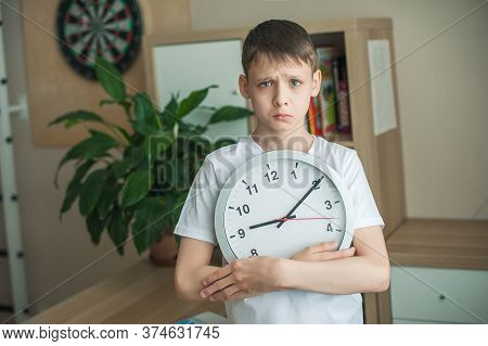 A Teenager Boy In A Childrens Room Stands With A Big Clock In His Hands With A Sad Face. The Concept