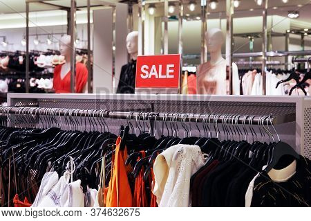 Sale Signboard In Clothing Store. Blurred Window Dummies On Background