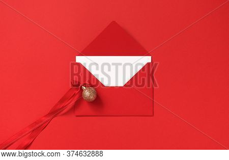 Red Envelope And Golden Glitter Christmas Ball With Bow From Atlas Ribbon On Red Background, Above.