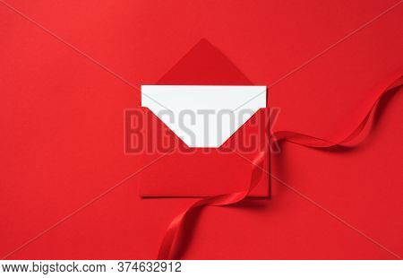 Mockup Envelope With Swirl Atlas Ribbon On Red Background, Top View. Template Empty White Paper Card