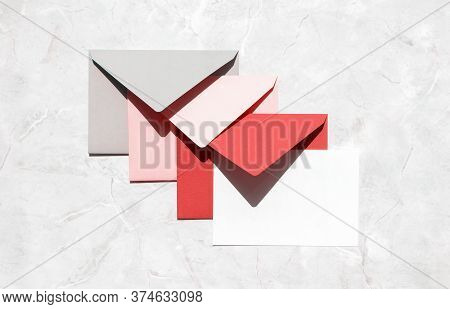 Stack Of Gray, Pink, Red Mail Envelopes And Empty White Paper Card On Marble Stone Table, Top View.