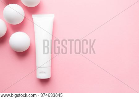 Cream Lotion Container Tube And White Ping Pong Balls On Cute Pink Background. Abstract With Geometr