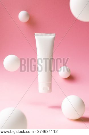 Levitation White Plastic Tube For Cosmetic Product On Pink Background With Abstract White Spheres, F