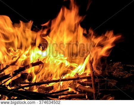 Bonfire On Ivan Kupala.  Bonfire With Branches At Night In The Forest. Tongues Of Fire. Flames Of Fi