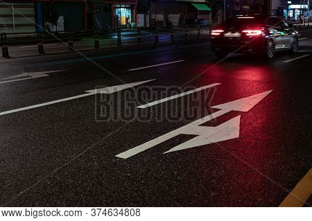 Arrows On Road Markings At Night. Pointers For Cars On The Road On Wet Asphalt. Car With Brakes On W