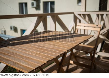 Wooden Table With Chairs Stands On The Balcony Of The Motel. Wooden Table At A Motel In Sunny Weathe