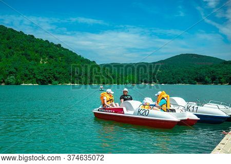 Sukko, Russia - 03.06.19: Group Of Tourists In Life Jackets On A Catamaran Depart From The Shore. Re