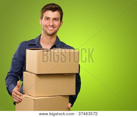 A Young Man Holding A Stack Of Cardboard Boxes On Green Background