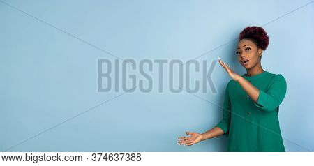 Holding Blank Copyspace. African-american Young Womans Portrait Isolated On Blue Studio Background.