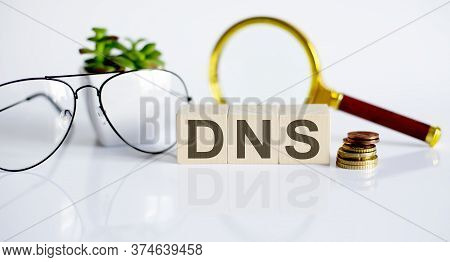 Dns Concept On Wooden Cubes And Flower ,glasses ,coins And Magnifier On White Background
