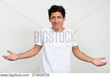 Portrait Of Happy Hispanic Man Shrugging Shoulders
