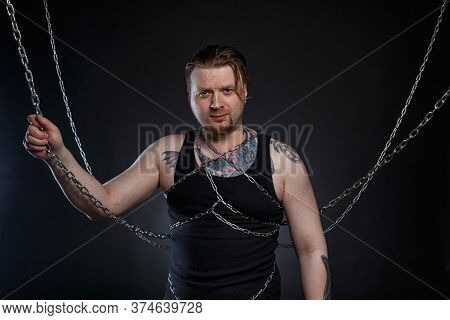 Photo Of A Tattooed Man Bound In Chains