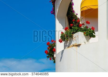 White Balcony With Red Flowers Against Bright Blue Sky, Puerto De La Cruz, Tenerife, Spain