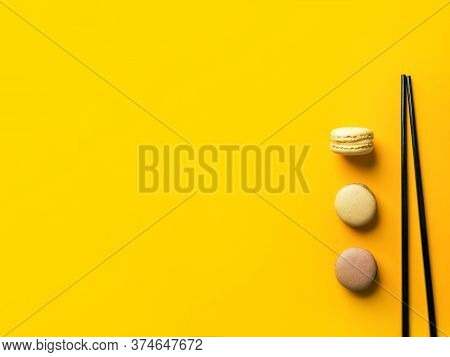 Coffee Mocha Caramel Macarons Laid Out In Vertical Row On Bright Yellow Background With Black Chopst