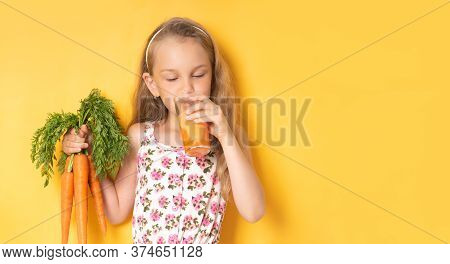 Pretty Little Girl In A Gown With Floral Patteern Drinking Carrot Juice Holding Bunch Of Carrots In