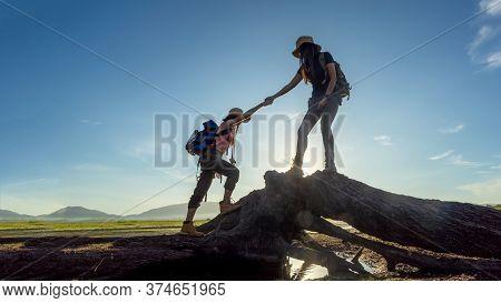Group Hiker Team Woman Helping Her Friend Climb Up Timber. Traveler Teamwork And Family Relax Walkin