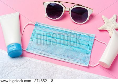 Medical Mask With Sunscreen Cream On Pink Background. Coronavirus Summer Concept