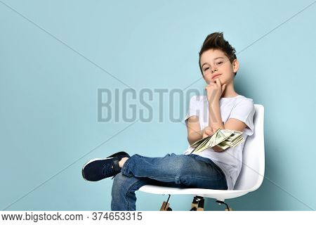 Concentrated Guy Sits On Chair Holding Dollars And Touching Chin With Hand Thinking How To Earn More