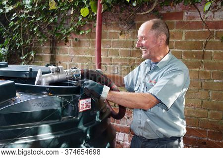 Buckingham, Uk - September 13, 2014. Man Filling A Bunded Oil Tank With Domestic Heating Oil (kerose
