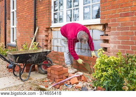 Buckingham, Uk - March 15, 2016. Bricklayer Building A Wall On A Uk Heritage House While Installing
