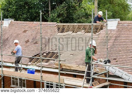 Buckingham, Uk - September 06, 2016. Builders Or Roofing Contractors Removing, Replacing Old Tiles O